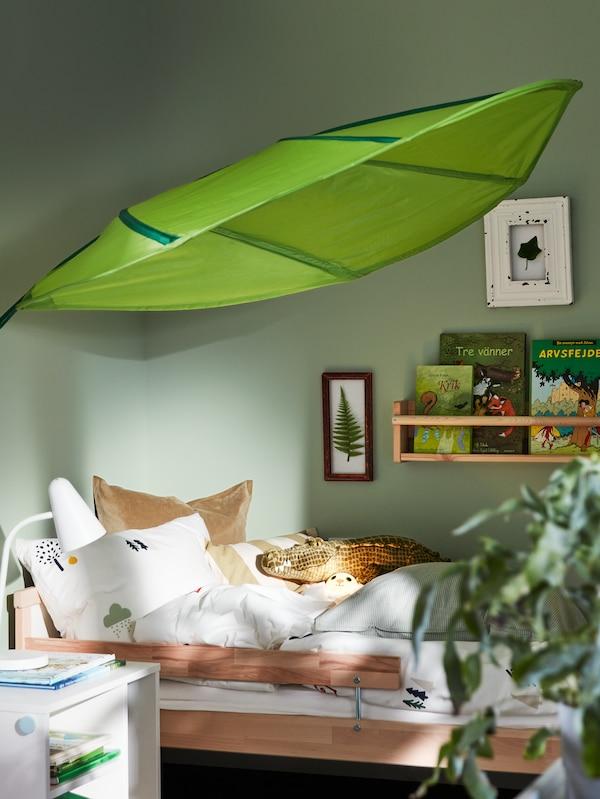 Egy gyerekszoba sarkát látjuk, benne SNIGLAR ágykerettel, felette falipolcot könyvekkel, valamint egy nagy, levélformájú, zöld LÖVA baldachint.