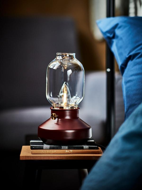 Stolová lampa, ktorá vyzerá ako klasický lampáš, na nočnom stolíku s knihami vedľa postele s modrými posteľnými obliečkami.
