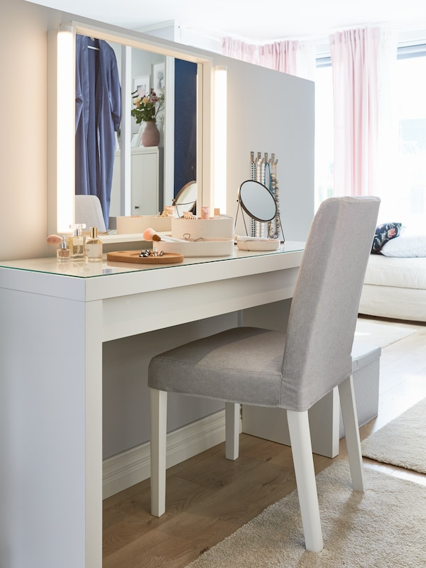 Et hvidt sminkebord, en grå polstret stol, et spejl med lys i siderne, parfume, makeup og toiletartikler.