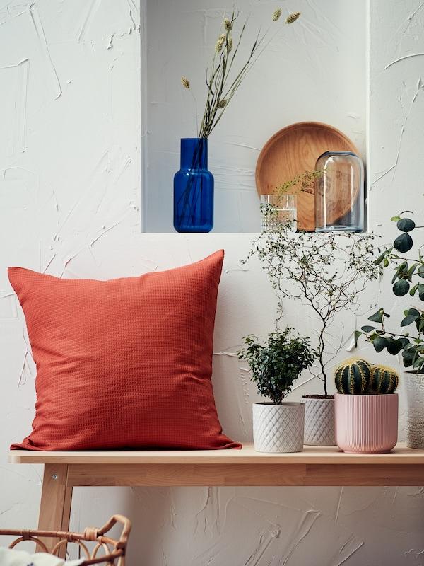 Planter og en pude med EBBATILDA pudebetræk på en bænk under en niche, hvor der står en vase og andre ting.