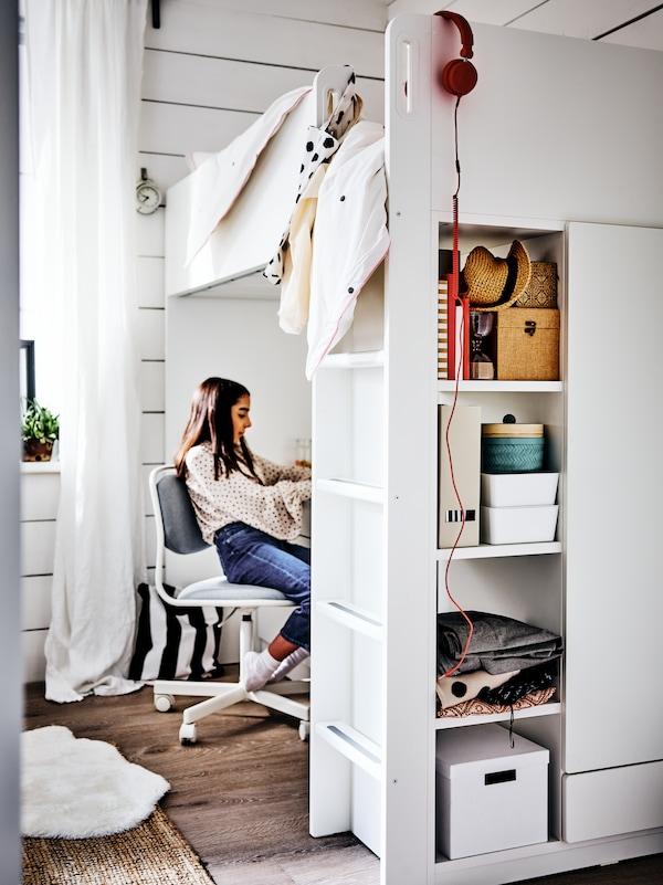 Une jeune femme assise sur une chaise ÖRFJÄLL devant un bureau, sous un lit mezzanine SMÅSTAD. Des boîtes sont rangées sur les tablettes du cadre de lit.