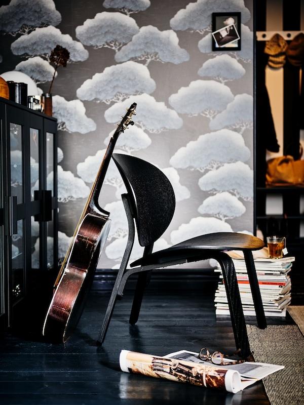 Teil eines Raumes mit gemusterter Tapete, u. a. mit einem dunklen Holzboden und einer Gitarre, die an einem schwarzen Stuhl lehnt.