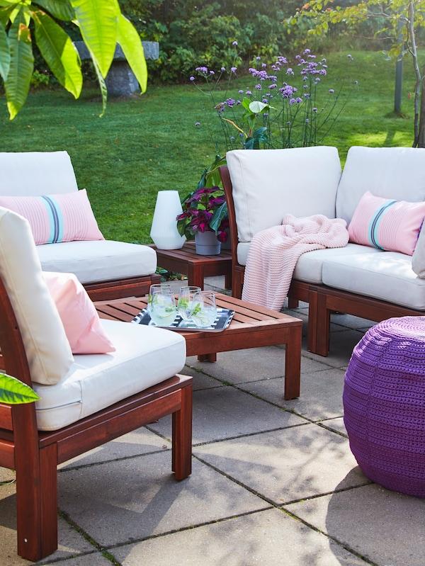 Egy fából készült dohányzóasztal a szabadban, fából készült kanapéval és fehér kárpitozású fotelekkel, rózsaszín párnákkal és egy takaróval, lila puffal.