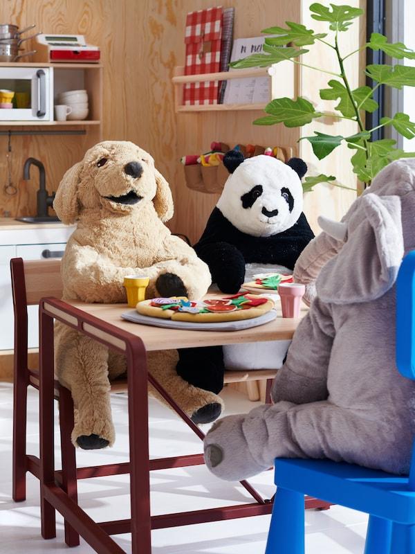 Des animaux en peluche sont assis à une table pour enfants dans une salle de jeux.