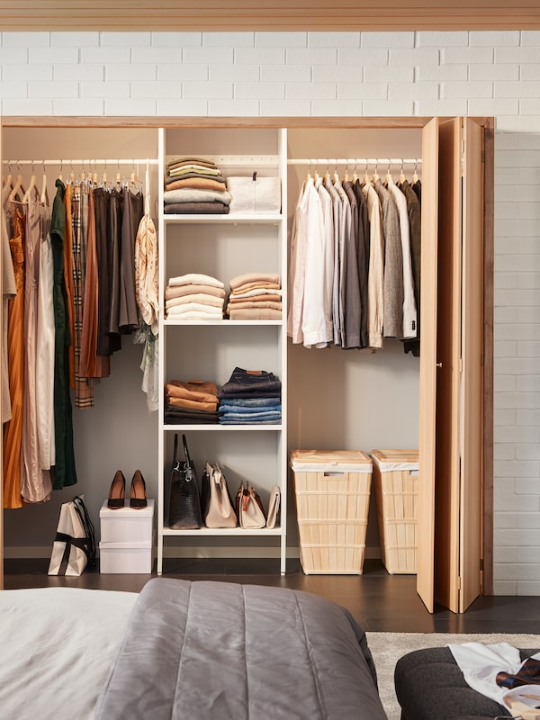 An AURDAL wardrobe combination with shelves, clothes rails and foldable wooden doors which is built into a space in the wall.