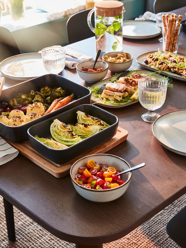 Tavolo da pranzo in legno con due teglie da forno nere contenenti verdure, ciotole con pomodori in insalata, due piatti e altri oggetti.