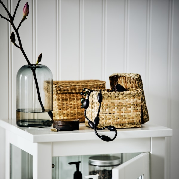 Deux boîtes LURPASSA en jonc de mer près d'un vase sur une armoire haute HEMNES. Une des boîtes est ouverte et un collier en sort.