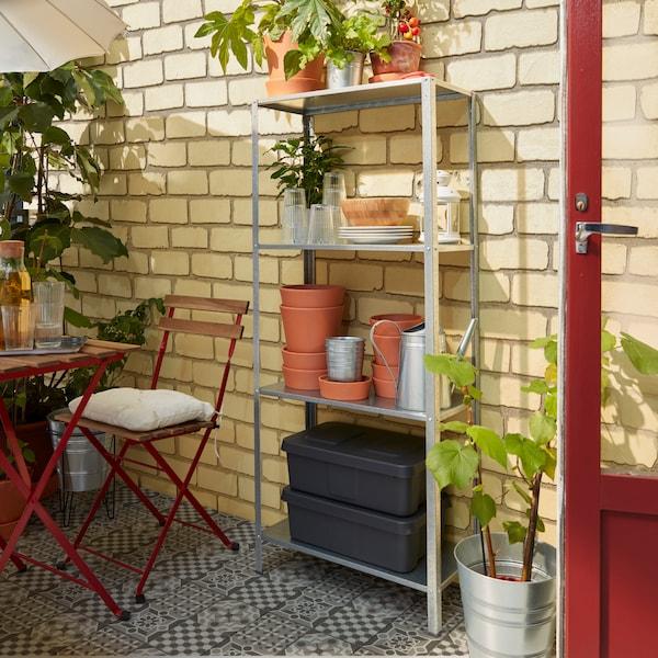 Tuinkast met plantenpotten en planten en een tuinset