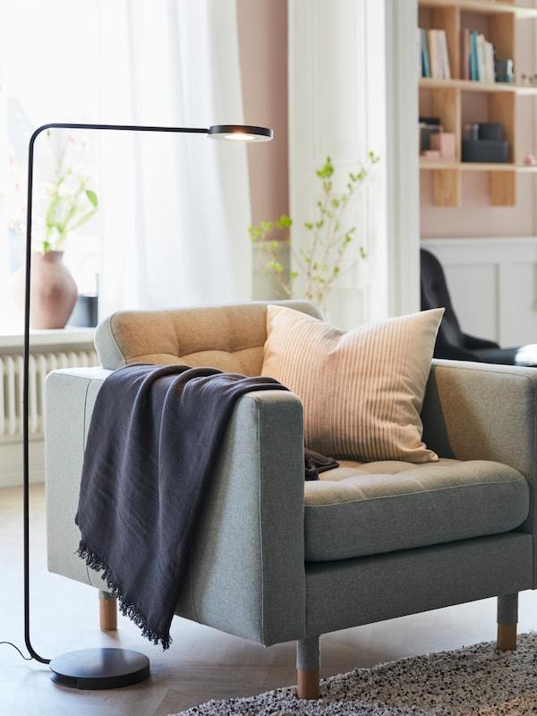 IKEA YPPERLIG LED black floor lamp, providing light to an LANDSKRONA armchair.
