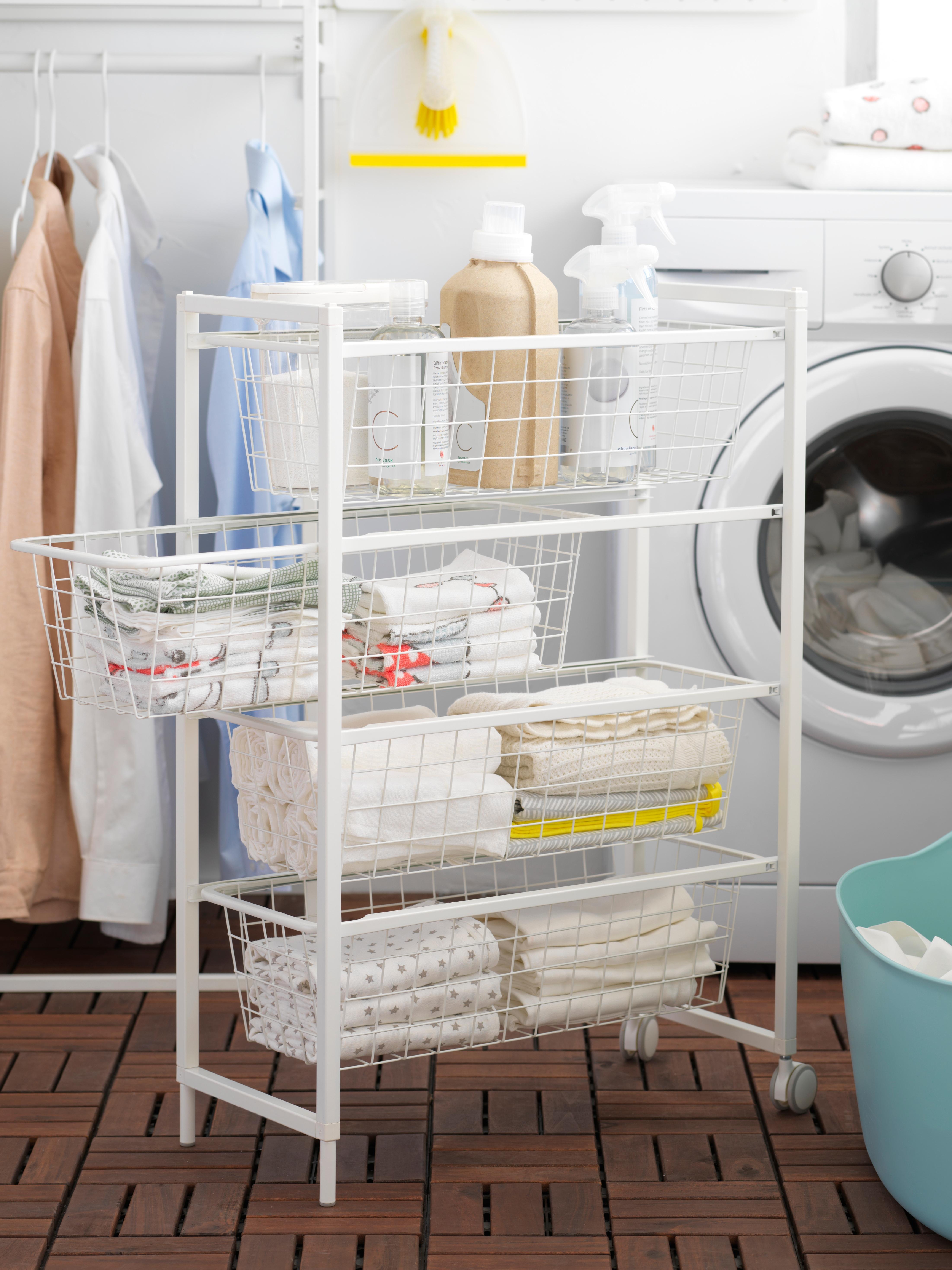 In een wasruimte staan een wasmachine en een wit JONAXEL frame met draadmanden en wielen, met daarop handdoeken en zeep.