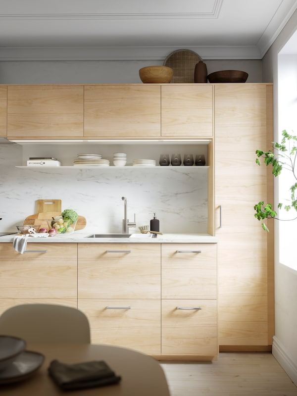 A METOD kitchen with wooden fronts and doors, chrome handles and white marbled splashbacks. Tableware on an open shelf.
