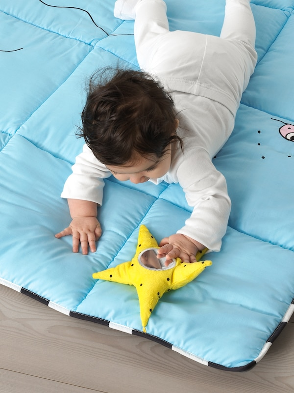 A baby lying on a blue KLAPPA play mat wearing white clothes, holding a yellow star.