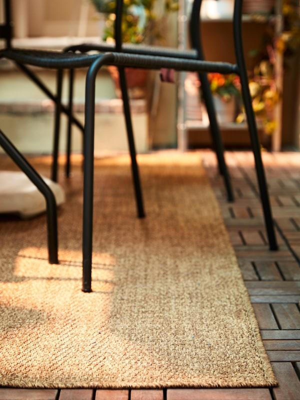 Ein mittelbrauner, flach gewebter Teppich auf einem Bodenrost in Holzoptik. Darauf stehen graue Stühle für draussen.