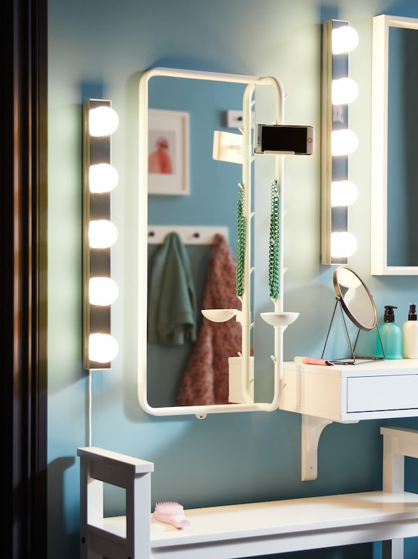 Des appliques à DEL en acier inoxydable LEDSJÖ avec un miroir MÖJLIGHET, un miroir NISSEDAL et un banc range-chaussures blanc HEMNES.