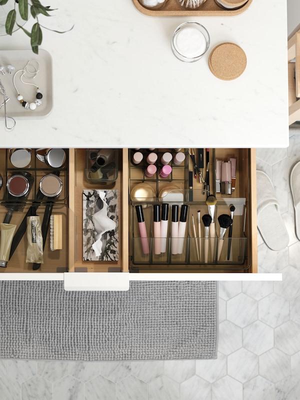Kabinet sink dalam kesan marmar putih. Laci terbuka yang terdapat produk kecantikan disusun dengan kemas di dalam kotak GODMORGON.