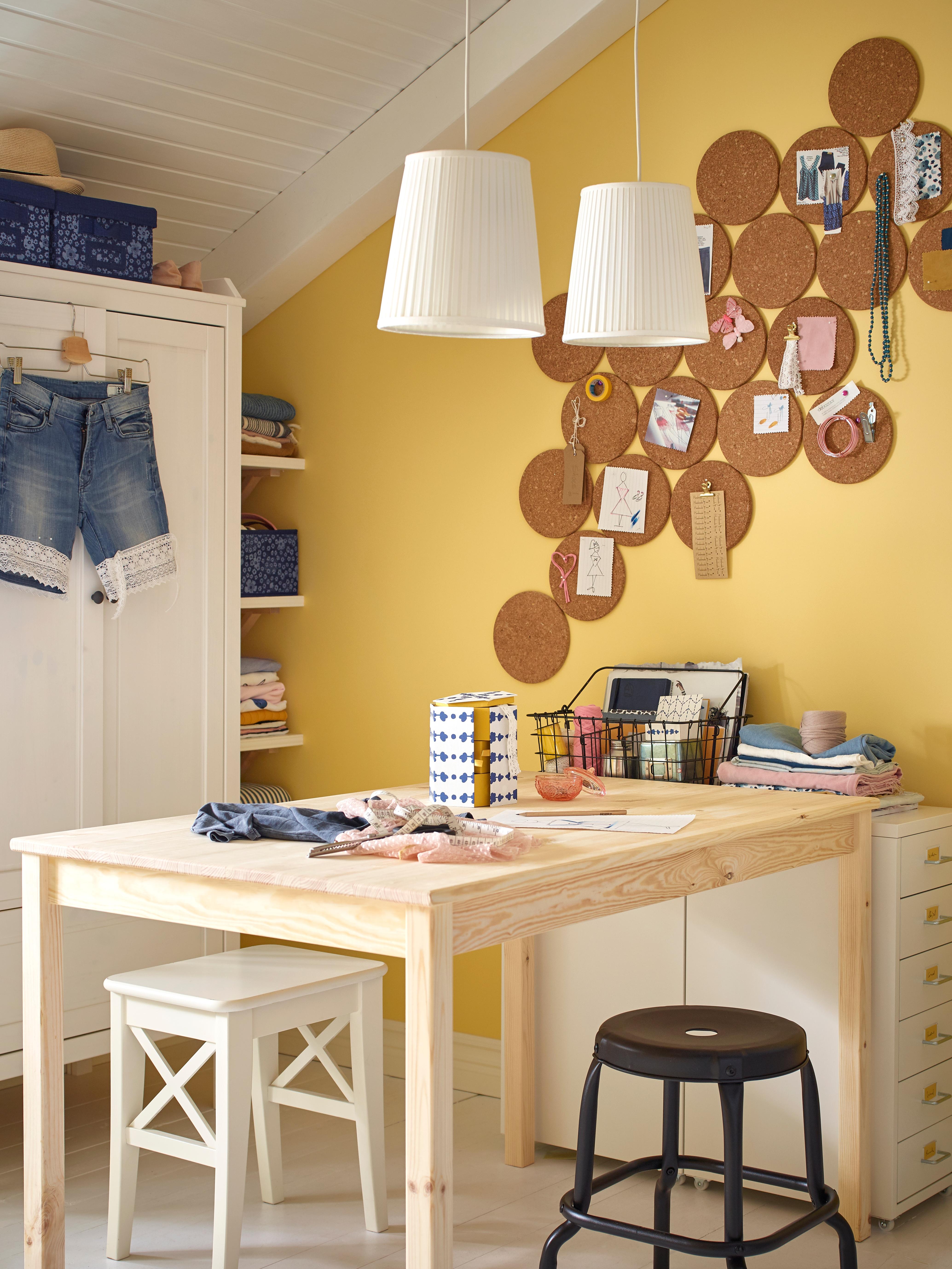 INGO stol od bora na kojem se odvija projekt šivanja uz dvije stolice, dvije visilice, bijeli ormar i metalne ladice.