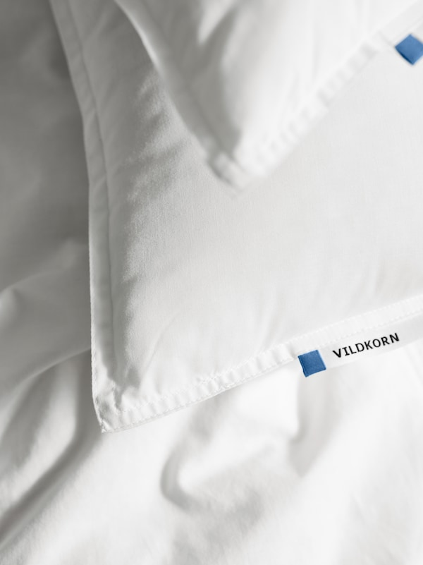 The corners of two VILDKORN pillows, one on top of the other, lying on white bed linen with the product name label showing.