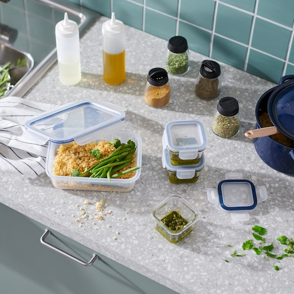 Overhead view of a counter with plastic containers holding prepared meals, with spice containers in the background.