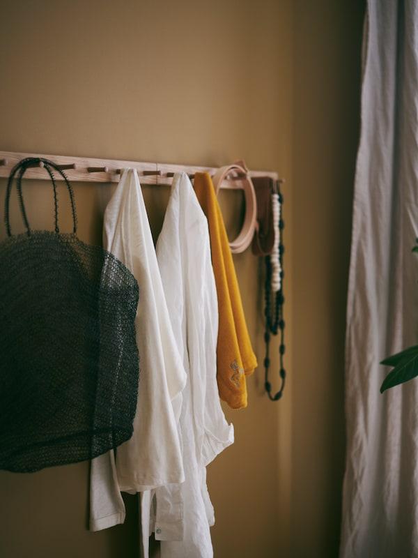 ملابس وحقيبة وإكسسوارات متنوعة بألوان متنوعة معلقة على علاقة HÖVOLM بـ (6) مقابض.