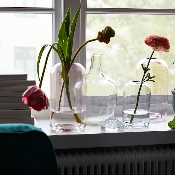Glass flower vases and bottle sitting on a window ledge in front of a window, some of them have flowers in them.