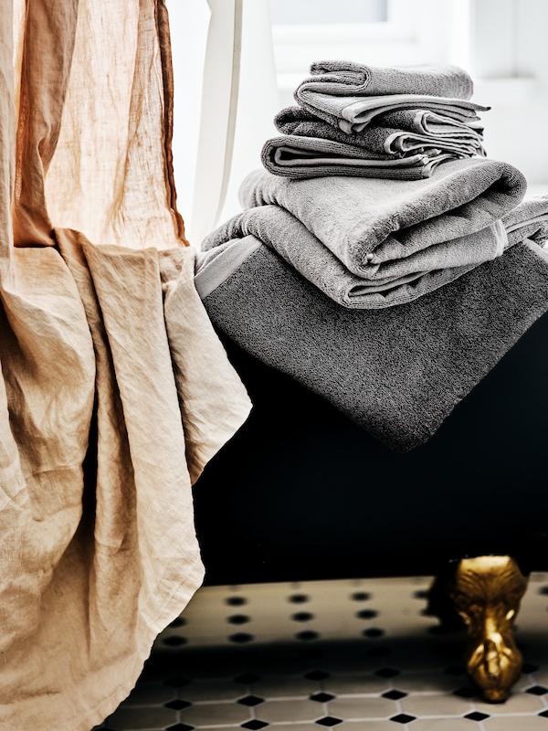 Une pile de serviettes noires et gris clair à côté d'une baignoire îlot noire sur pieds dorés, avec un rideau de douche beige.