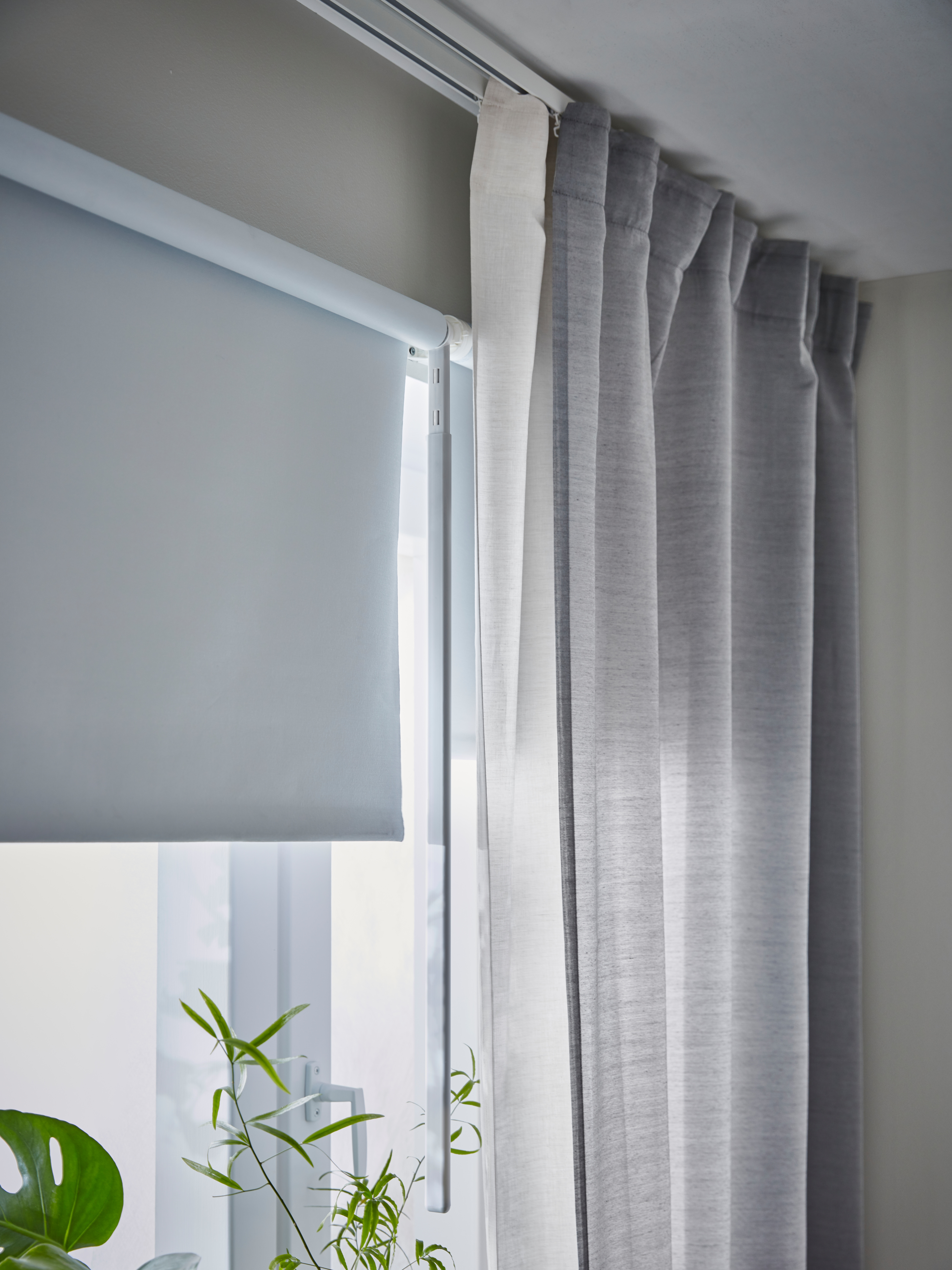Bedroom with light grey wall, roller blind with block-out coating mounted on window frame, grey curtains, green house plants.