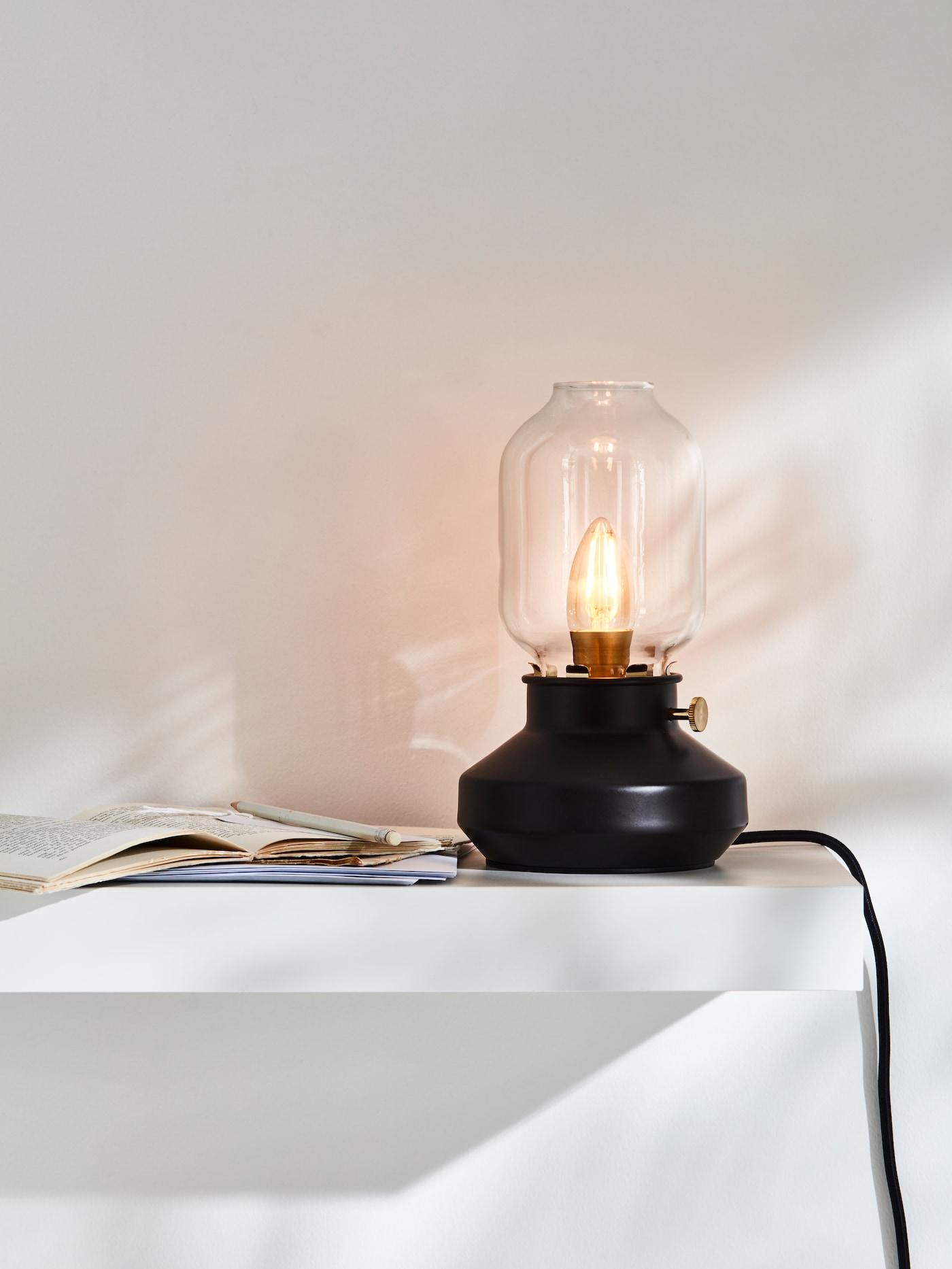 Светильник, выполненный в форме старинного подсвечника, стоит на белой полке рядом с открытой книгой.