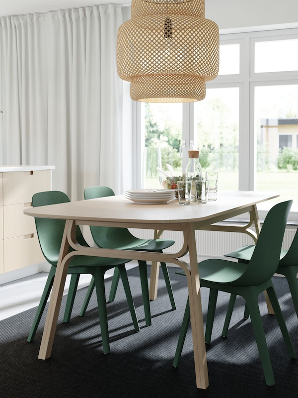 A dining table, a pendant lamp and kitchen drawer fronts in bamboo, green chairs, a dark grey rug and white curtains.