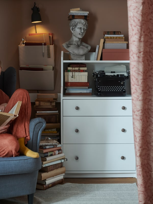 A white bookcase with drawers and shelves filled with old books, a typewriter and a sculpted bust placed by a reading corner.