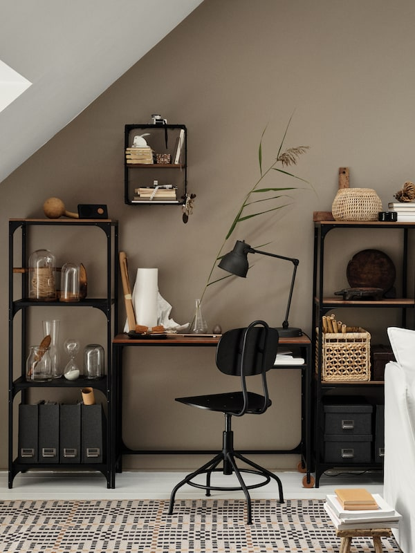 Meja komputer riba beroda di antara dua unit rak berwarna hitam, kerusi pusing berwarna hitam, para dinding kesan antik berwarna hitam/kayu pain.