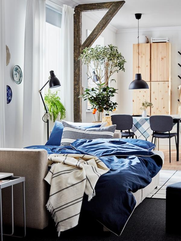 Un divano letto beige pronto per la notte con biancheria blu scuro/bianca, un plaid a righe, lampade nere e un tappeto grigio.