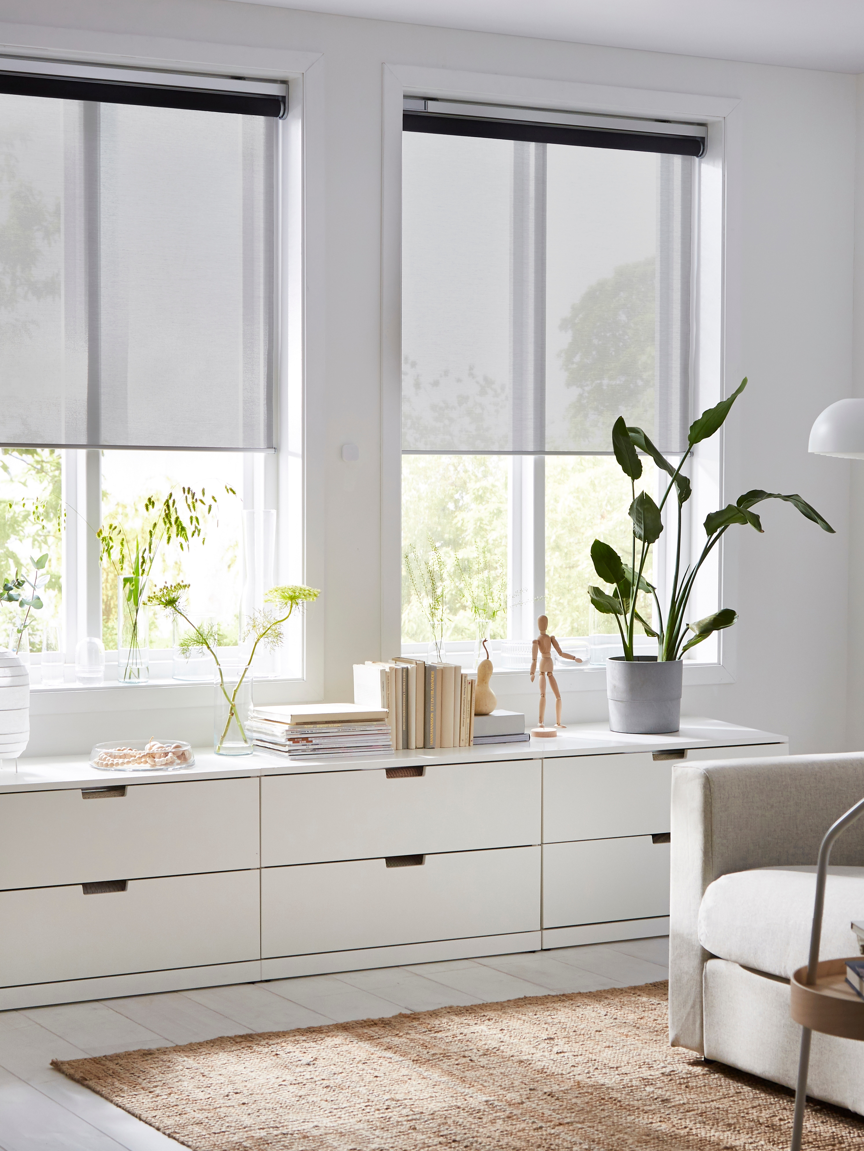 A living room with two windows covered in SKOGSKLÖVER blinds. Below the windows are three NORDLI drawer units holding plants.