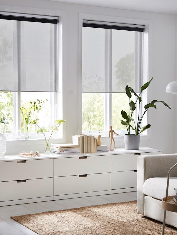 Obývacia izba s dvomi čiastočne stiahnutými roletami KADRILJ na dvoch oknách nad nízkymi komodami.