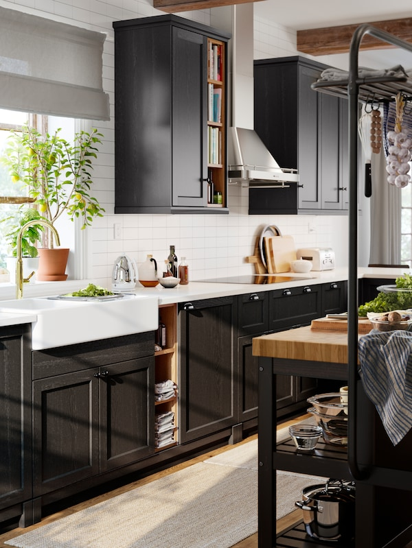 A rustic kitchen with black cabinets, a white sink with a visible front and a brass-coloured tap.