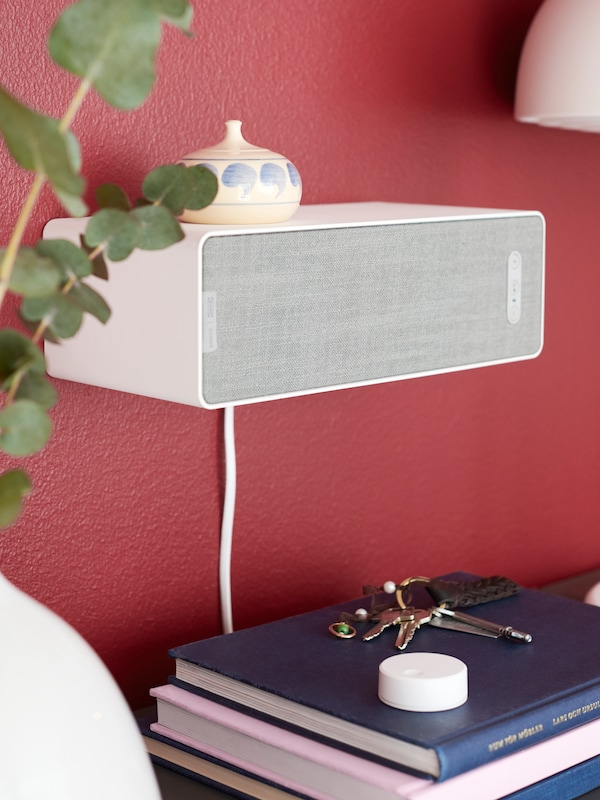 A white SYMFONISK attached to a wall and used as a shelf