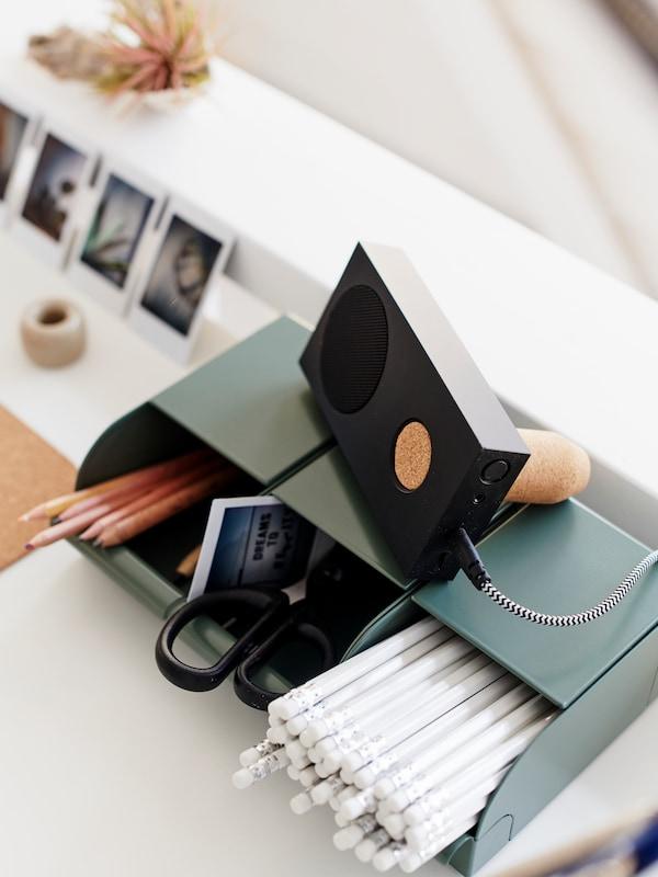 na cassa Bluetooth appoggiata su un contenitore in cui sono organizzati un taccuino, matite e forbici, su una superficie.