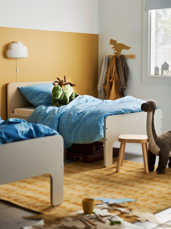 Two SLÄKT extendable beds with duvets with blue MÖJLIGHET quilt covers stand in a bedroom with large toy dinosaurs.