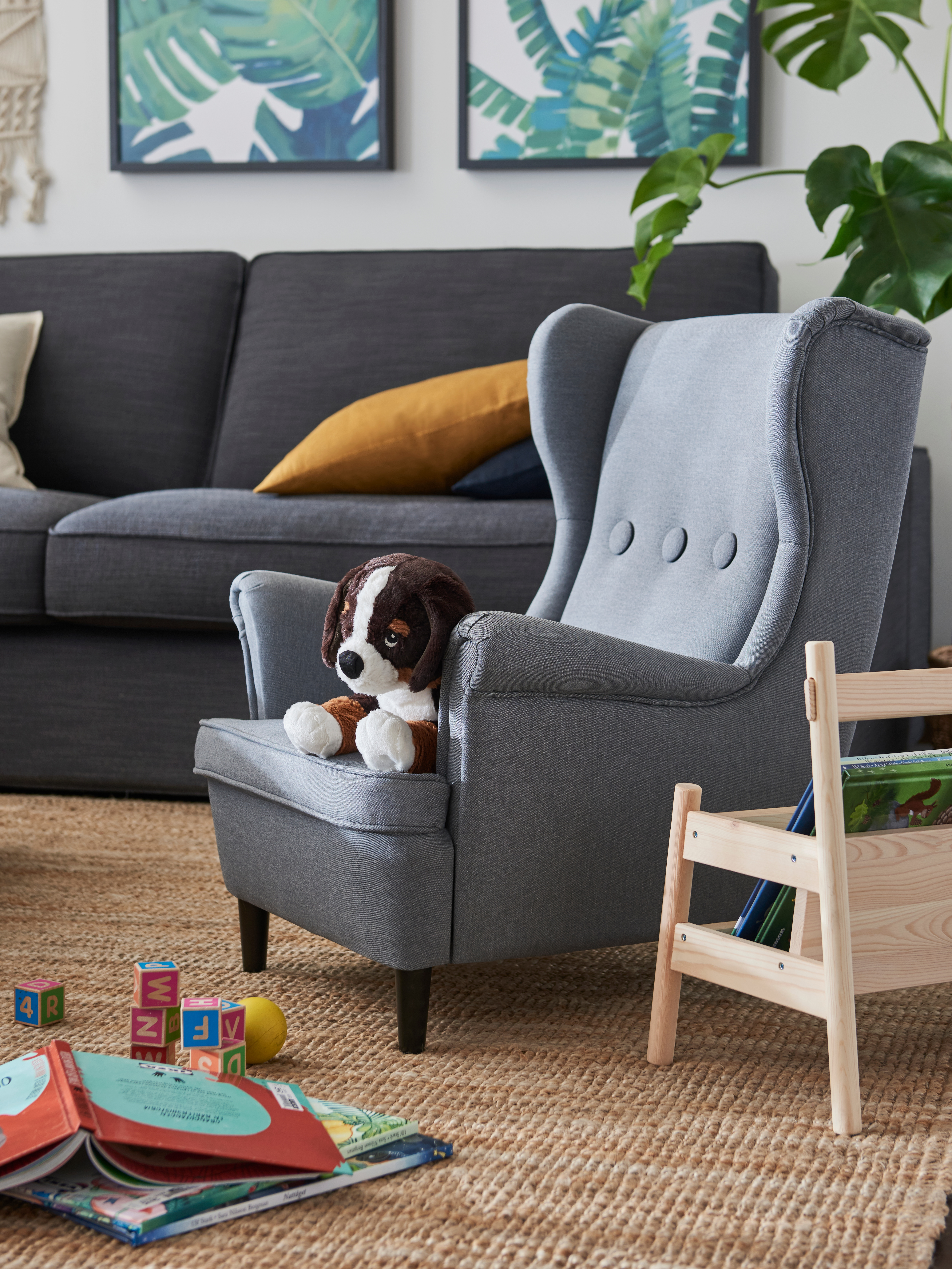 Living room with children's armchair, soft toy, three-seat sofa, book display, book, flat-woven rug, frames, green plants.