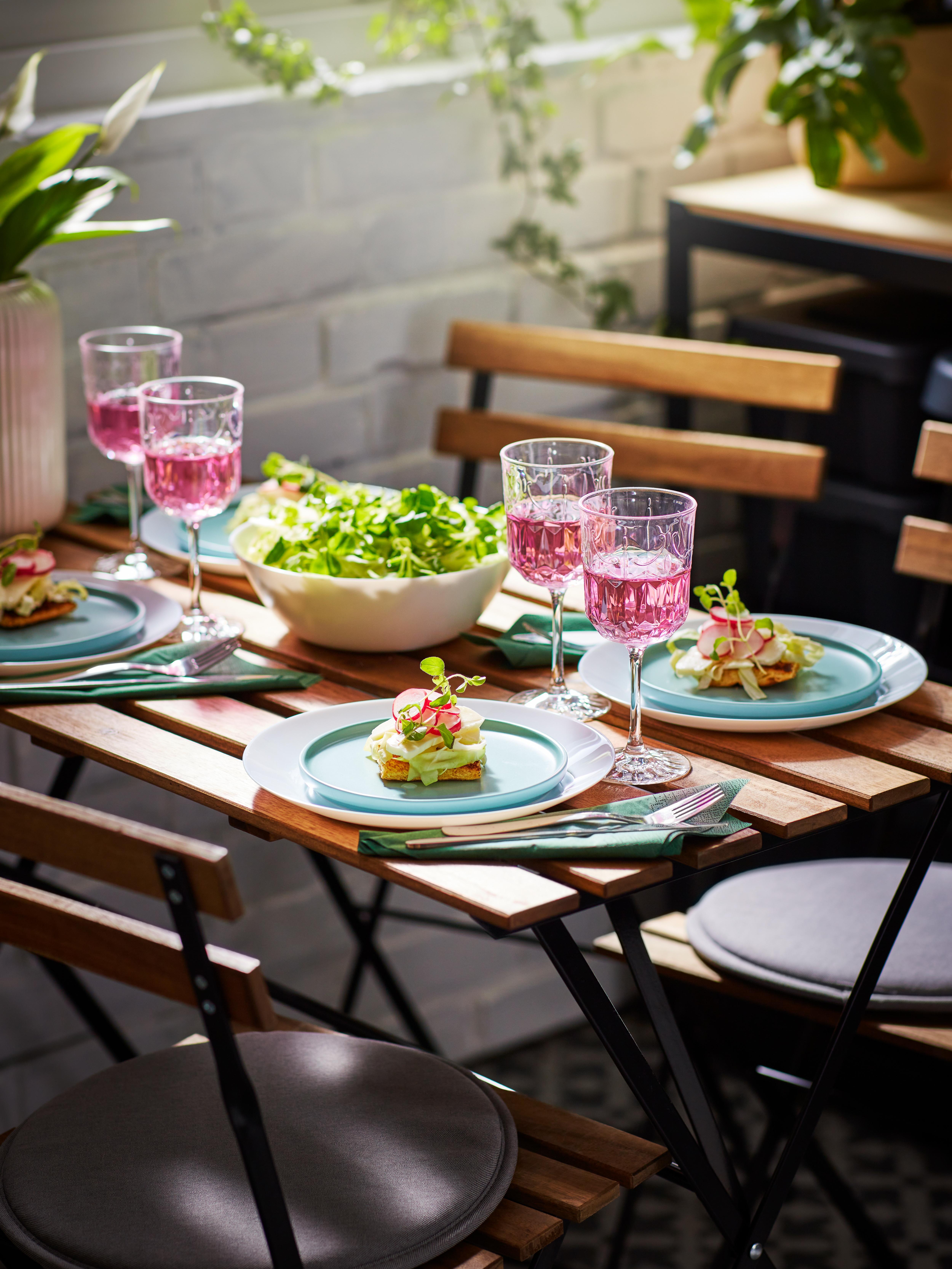 Une table de jardin pour un petit repas; des verres à vin, de la salade dans un bol OFTAST blanc et des entrées sur des assiettes KEJSERLIG turquoises.