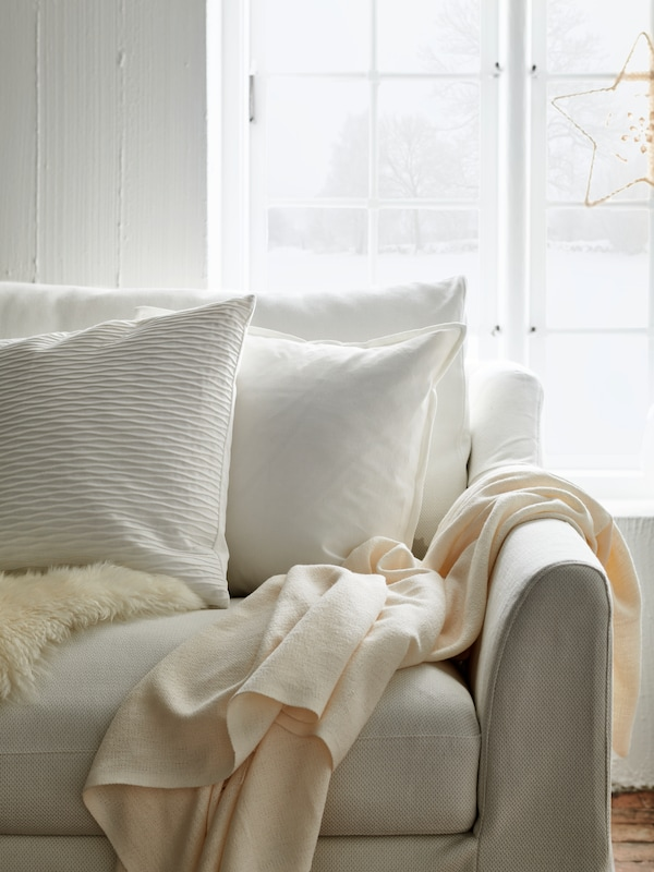 A beige sofa with white cushions and a throw laid on it, a window behind with white curtains and an ornamental star.