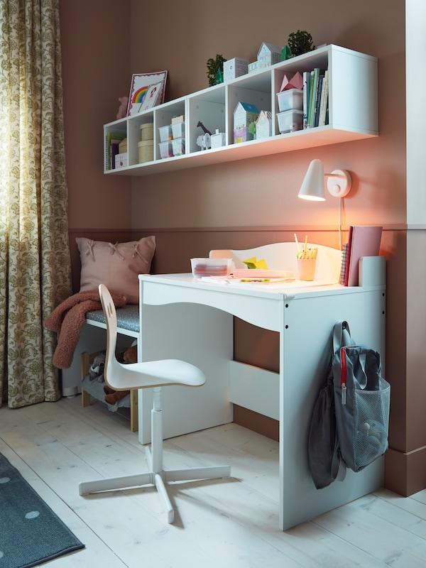 Une chaise pivotante enfant VALFRED/SIBBEN est installée devant un bureau SMÅGÖRA blanc, près de deuxétagères SMÅGÖRA fixées au mur.