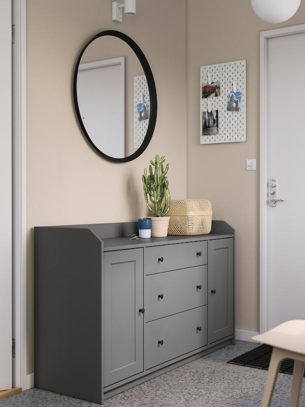 Szary kredens HAUGA ustawiony przy drzwiach wejściowych w korytarzu, z wiszącym nad nim lustrem i ustawionymi na nim pudełkiem i rośliną w doniczce.
