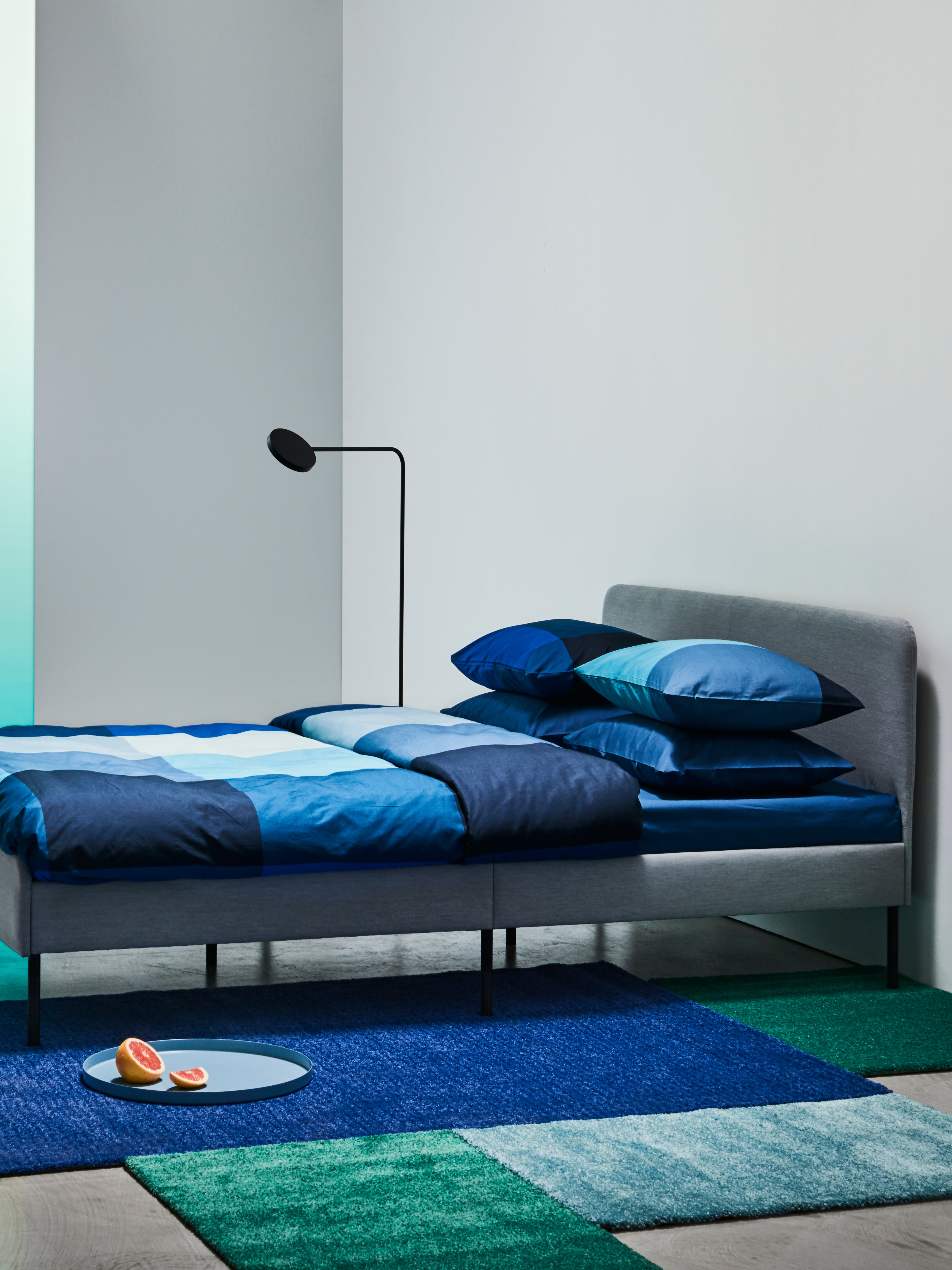 A SLATTUM upholstered bed frame in grey, with bedding in various shades of blue and a floor lamp beside the bed.
