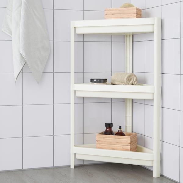 O baie placată cu faianță albă, cu o poliță de colț VESKEN cu diverse obiecte, cum ar fi cutii de lemn, pe rafturi.