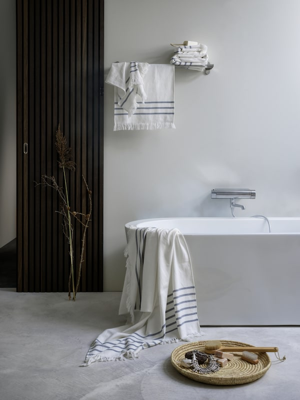 A bathroom with SIESJÖN towels in different sizes draped over the bath and hanging or folded on a towel rail above the bath.