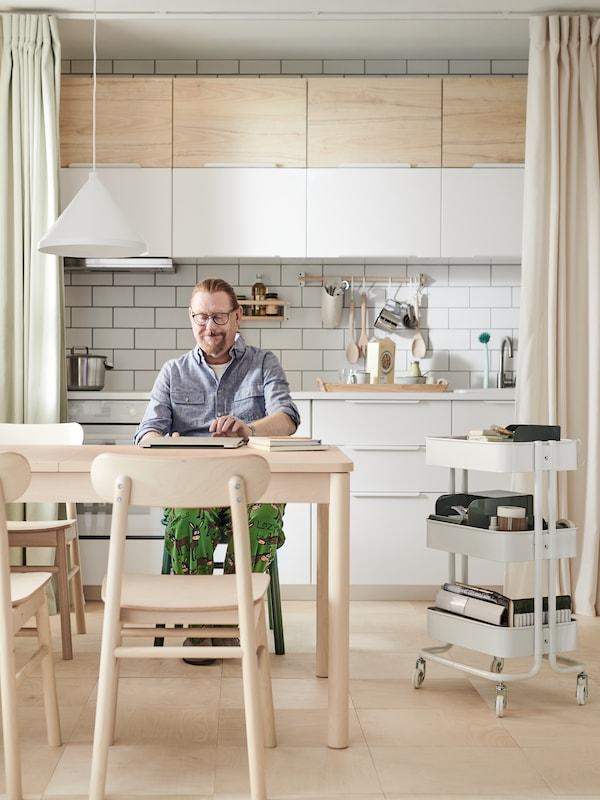 Mężczyzna siedzący z laptopem przy stole w kuchni