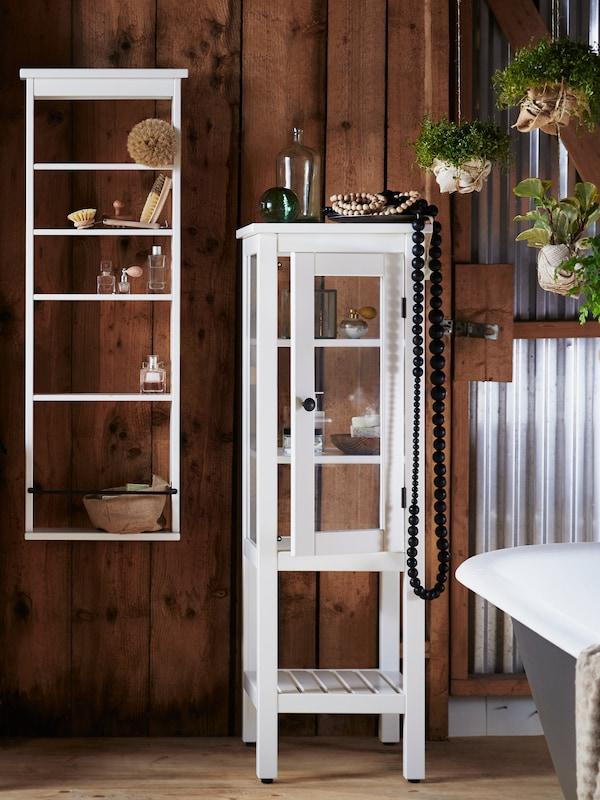 Estante VILTO em bétula, colocada entre dois lavatórios, com toalhas, uma coluna de som e produtos de beleza.