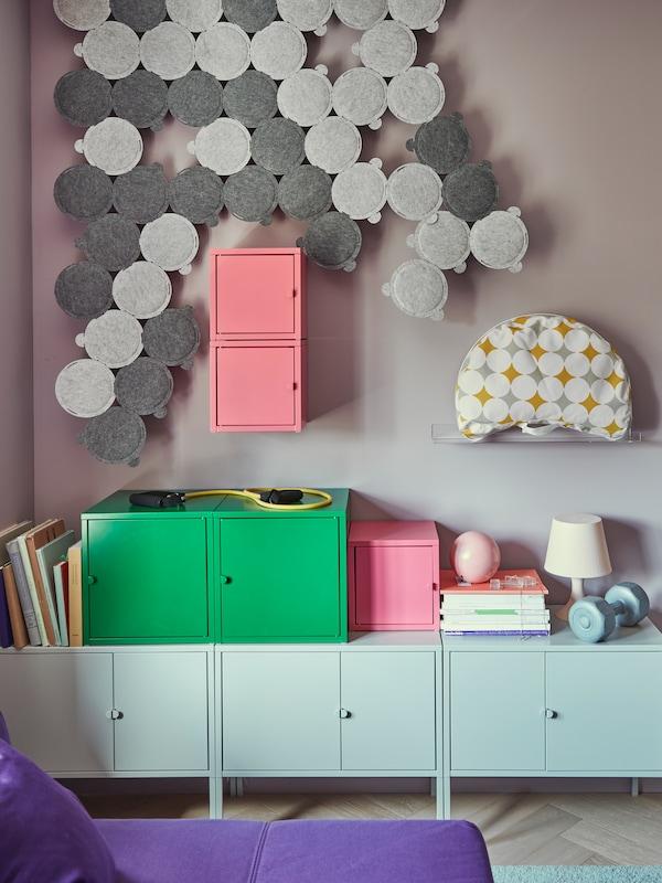 Une œuvre d'art faite de panneaux acoustiques ODDLAUG est suspendue à un mur au-dessus d'armoires en métal LIXHULT dans un salon.