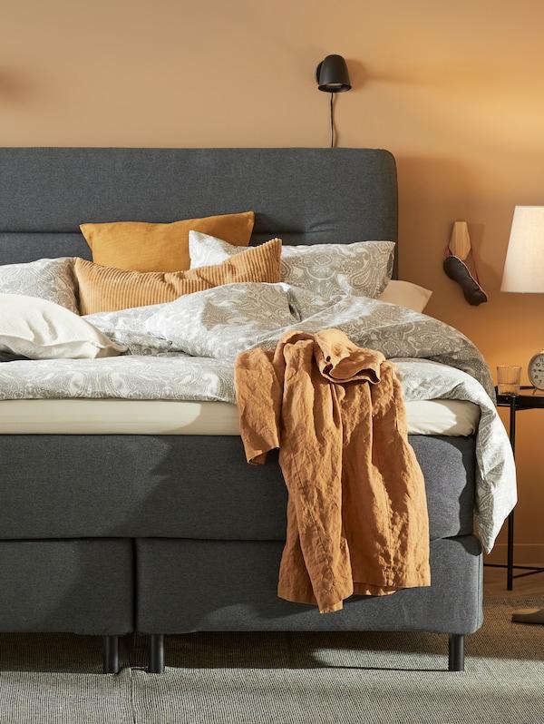 Dormitorio con paredes amarillas y un diván cama FINNSNES gris con ropa de cama JÄTTEVALLMO en blanco/gris.