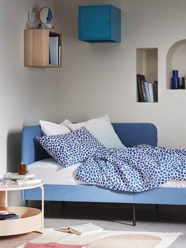 Quarto com cama acolchoada BLÅKULLEN em azul médio com cabeceira de canto, mesa de centro e dois armários EKET.